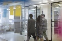Business people walking and talking in office corridor — Stock Photo