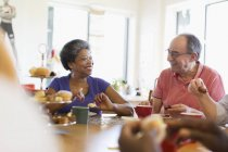 Happy senior friends enjoying afternoon tea in community center — Stock Photo