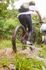 Женщина катается на горном велосипеде по грязной тропе — стоковое фото
