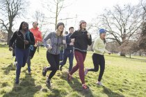 Улыбающиеся бегуньи бегают в солнечном парке — стоковое фото