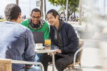 Male friends using laptop at sunny sidewalk cafe — Stock Photo