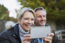 Mature caucasian couple taking picture in park — Stock Photo