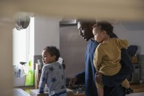 African american father with kids at kitchen — Stock Photo