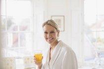 Portrait souriant, confiante femme d'âge mûr en peignoir boire du jus de — Photo de stock