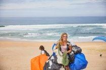 Ritratto sorridente, parapendio femminile sicuro di sé con attrezzatura sulla spiaggia soleggiata dell'oceano — Foto stock