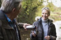 Mature caucasian couple drinking hot tea from thermos bottle in autumn park — Stock Photo