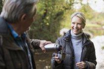 Reifes kaukasisches Paar trinkt heißen Tee aus Thermosflasche im Herbstpark — Stockfoto