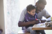 Happy father and toddler son coloring at table — Stock Photo