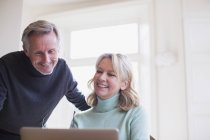 Smiling mature couple using laptop at modern home — Stock Photo