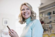 Portrait souriant, texto femme mature confiant avec téléphone intelligent — Photo de stock