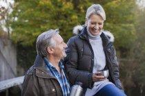 Mature caucasian couple drinking hot tea from thermos bottle in autumn park — Stock Photo