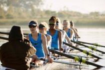 Female rowing team rowing scull on lake — Stock Photo
