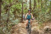 Беззаботная женщина катается на горном велосипеде по лесам — стоковое фото