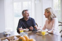 Smiling mature couple eating breakfast and talking at dining table — Stock Photo