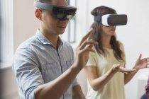 Programadores informáticos probando gafas de simulador de realidad virtual - foto de stock