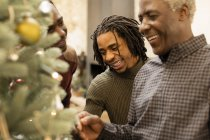 Smiling grandfather and grandsons decorating Christmas tree — Stock Photo