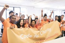 Portrait enthusiastic hackers cheering with banner, coding for charity at hackathon — Stock Photo