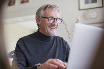 Smiling mature male freelancer working at laptop — Stock Photo