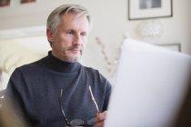 Focalizzato maturo freelance maschile che lavora al computer portatile a casa — Foto stock