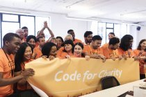 Hackers with banner coding for charity at hackathon — Stock Photo