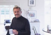 Portrait confident mature man drinking coffee in kitchen — Stock Photo