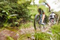 Человек катается на горном велосипеде, брызгает по грязной тропе — стоковое фото