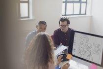 Дизайнери працюють, мозковий штурм комп'ютером в офісі — стокове фото