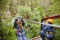 Happy woman zip lining above trees — Stock Photo
