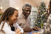 Smiling grandfather and granddaughter playing board game — Stock Photo