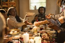 Family passing food at Christmas dinner — Stock Photo