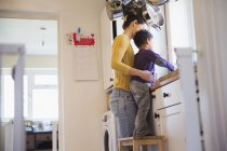 Happy caucasian mother with african american son at kitchen — Stock Photo