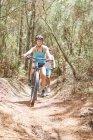 Женщина катается на горном велосипеде по солнечной тропе в лесу — стоковое фото