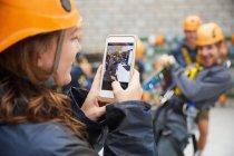 Frau mit Kamera-Handy fotografieren Freunde in Zip-Line-Ausstattung — Stockfoto
