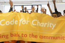 Hackers with banner cheering, coding for charity at hackathon — Stock Photo