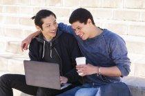 Casal gay masculino usando o laptop e a beber café — Fotografia de Stock