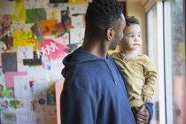 Afrikanische amerikanische Blick aus Fenster mit Sohn Vater — Stockfoto