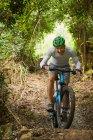 Happy man mountain biking on trail in woods — Stock Photo