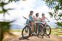Друзья-женщины катаются на горном велосипеде по солнечной полосе препятствий — стоковое фото
