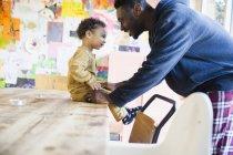 Seitenansicht eines afrikanisch-amerikanischen Vaters mit kleinem Sohn zu Hause — Stockfoto
