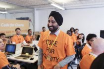 Happy, confident hacker in turban coding for charity at hackathon — Stock Photo
