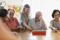 Volunteer helping senior man assembling jigsaw puzzle at table in community center — Stock Photo