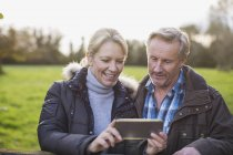 Mature caucasian couple using smartphone in autumn park — Stock Photo