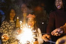 Playful girl with sparkler celebrating with family — Stock Photo