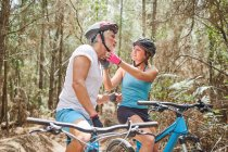 Fille aidant père avec casque de vélo de montagne sur le sentier dans les bois — Photo de stock
