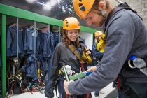 Man helping woman with zip line equipment — Stock Photo