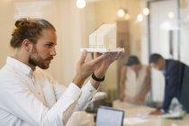 Focalizzato, curioso architetto maschio esaminando modello — Foto stock