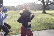 Confident female runner running in sunny park — Stock Photo