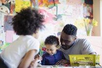 Padre e bambini piccoli colorano a tavola — Foto stock