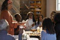 Frau, die mehr-Generationen-Familie an Weihnachtstisch Toasten — Stockfoto