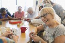 Glückliche Seniorin spielt mit Freundin am Tisch im Gemeindezentrum Karten — Stockfoto